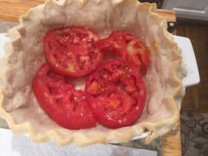 Tomatoes sliced thick, seasoned and layered with cheese and pesto sauce